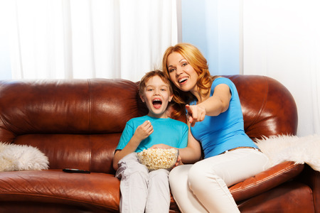Happy mother pointing forward and son laughing while eating popcorn are watching together TV and sitting on the brown sofa at home photo