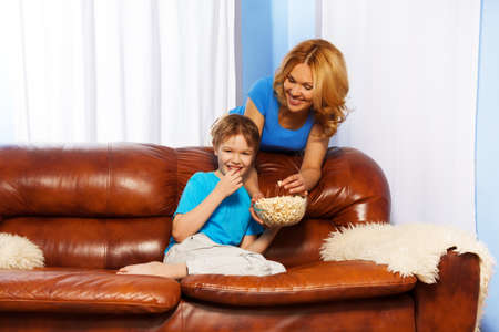 Laughing son eating popcorn and watching TV while happy mother looking at him and standing behind the back of brown sofa at home photo