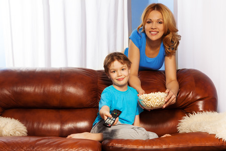 Happy mother with bowl of popcorn standing behind the back of brown leather sofa and her son with remote control sitting on the sofa are watching television together at home photo