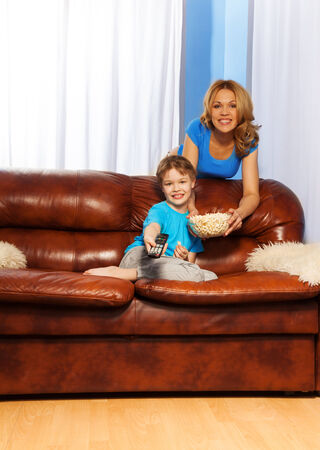 Smiling mother with bowl of popcorn standing behind the back of brown leather sofa with her happy son with remote control sitting on the sofa are watching television together at home photo