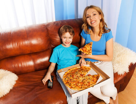 Happy boy and his mother eating pizza on the brown leather couch at home photo