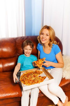 Laughing boy and his smiling mother eating pizza on the brown leather couch at home photo