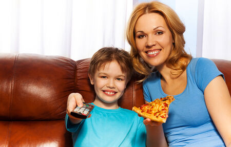 Happy boy switching remote control and his smiling mother eating piece of pizza on the brown leather couch at home photo