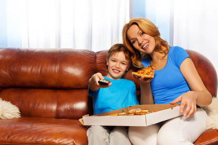 Happy boy switching remote control and his laughing mother eating piece of pizza holding the carton on her knees and sitting on the brown leather couch at home photo