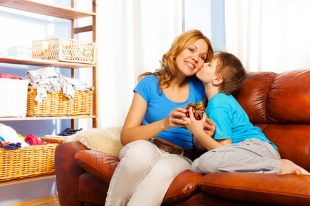 Beautiful family scene when boy is kissing his mother in cheek while giving gift to her on the brown leather sofa at home photo