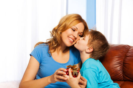 Beautiful family portrait of boy is kissing his mother in cheek while giving gift to her photo