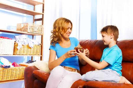brown leather sofa: Il ragazzo presenta un regalo alla sua madre, mentre guardando a lei sul divano in pelle marrone a casa