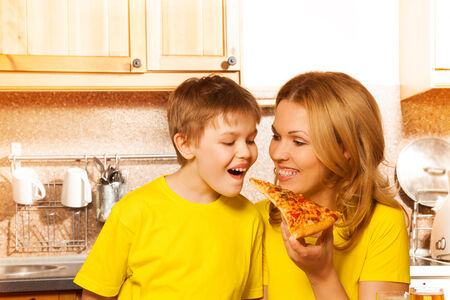 Cheerful mother feeding her smiling son with one hand with piece of pizza in the kitchen photo