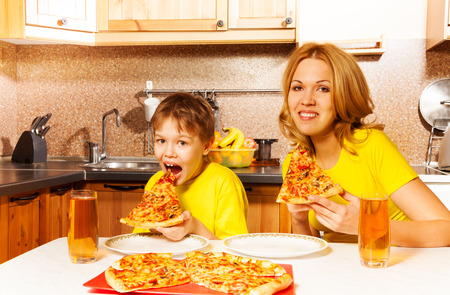 Hungry funny boy and his mother eating pizza together at the table in the kitchen