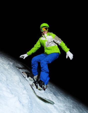 ski mask: Portrait of young woman standing on snowboard wearing ski mask at night