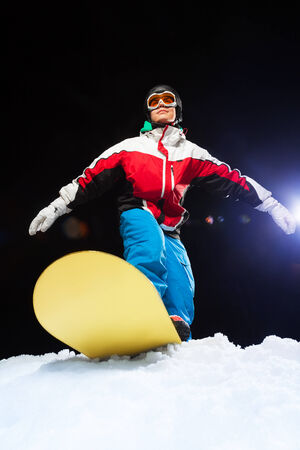 ski mask: Portrait of young snowboarder wearing ski mask ready to slide from mountain and balancing on the board at night