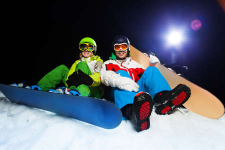ski mask: Two smiling snowboarders wearing ski masks sitting together at night with flash on the background