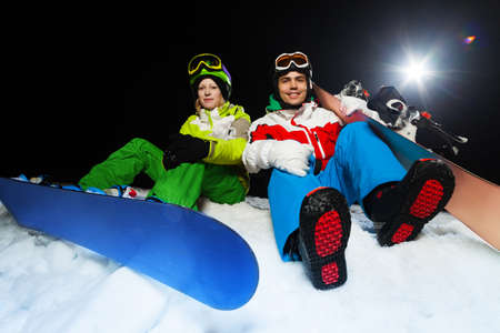 ski mask: Two smiling snowboarders of young man and woman sitting together at night with flash on the background