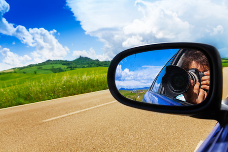 Photographer in car mirror shoots picture and drives on the road near green valley