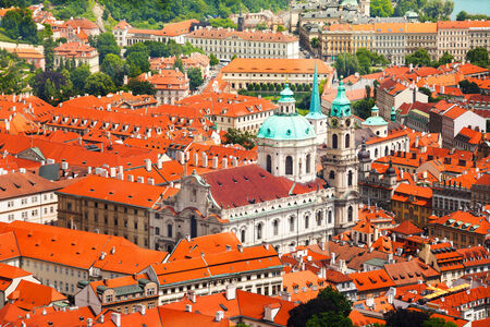 Church Of St. Nicholas With Red Roofs Houses View In Prague, Czech Republic  Stock