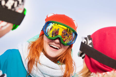 ski mask: Excited young woman in ski mask with two friends looking at her
