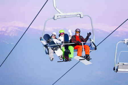 lift hands: Three excited young people with snowboarders sitting on ropeway on the mountains background
