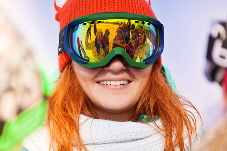 ski mask: Happy young woman in ski mask with reflection of her friends on the mask