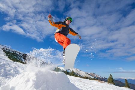 겨울에 산 언덕에서 스노우 보드 점프 남자
