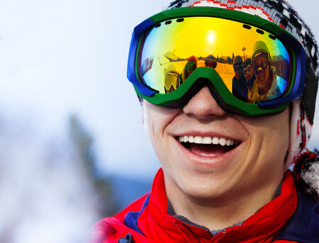 ski mask: Happy smiling snowboarder in ski mask portrait with reflection of his friends on the mask Stock Photo