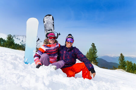 Sitting couple in ski masks on the snow with snowboards standing behind photo