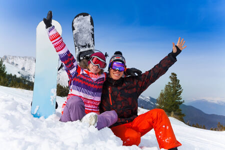 Excited couple sitting with hands up in the air with snowboards on the background photo