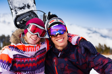 Hugging couple in ski masks together on the snow with snowboard behind photo