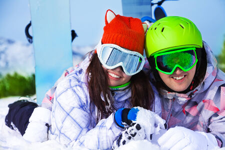 Happy young couple in ski masks together on the snow looking straight photo