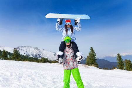 ski mask: Man in ski mask holding girl with holding  board with arms up her head