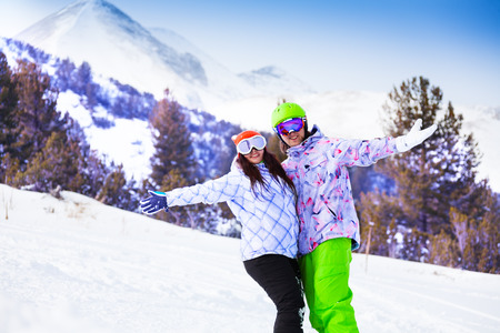 Smiling woman and man hugging each other with one hand wearing ski masks and embracing with other hand photo