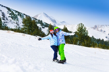 Two snowboarders standing close to each other and embracing their hands photo