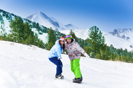 Two friends standing on snowboards balancing while holding each other with second arm photo