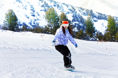 ski mask: Girl in ski mask sliding with snowboard and balancing with hands