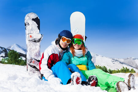ski mask: Couple in ski mask sitting on snow and snowboarders standing behind Stock Photo