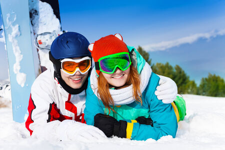 Cuddling couple in ski masks lying on the snow together photo