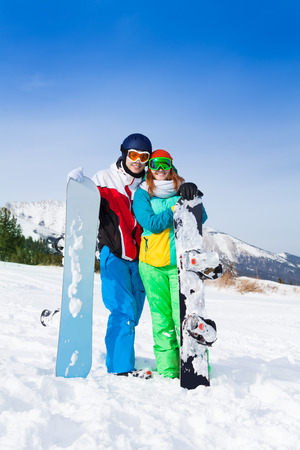 Smiling couple in ski masks standing together on the snow in ski resort photo