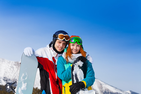 Smiling young couple with snowboards in the mountains photo