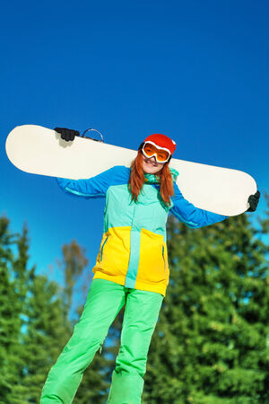 ski mask: Woman in ski mask standing with snowboard in winter with fir trees on the background