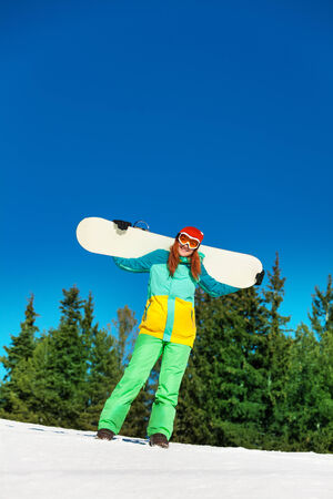 ski mask: Happy girl in ski mask standing with snowboard in winter with fir trees on the background