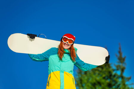 ski mask: Smiling girl in ski mask standing with snowboard in winter with fir trees on the background Stock Photo