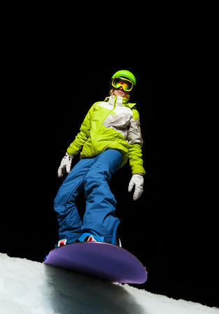 ed5e3ddc5b61 Portrait of girl wearing ski mask ready to slide with snowboard down the  mountain at night