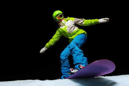 ski mask: Woman wearing ski mask balancing with hands on snowboard and ready to slide down at night Stock Photo
