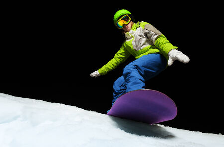 ski mask: Portrait of young woman wearing ski mask balancing with hands on snowboard and ready to slide down at night Stock Photo