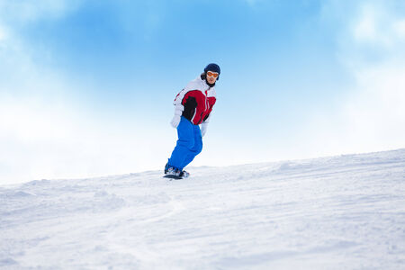 Man riding on the snowboard down mountain hill in mountains photo