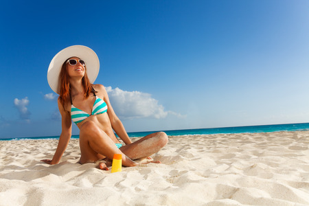 Tanned girl in blue striped bikini relaxing on sunny beach Stock Photo