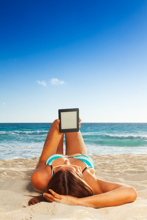 blank tablet: Tanned young woman laying on sandy beach and reading her ebook