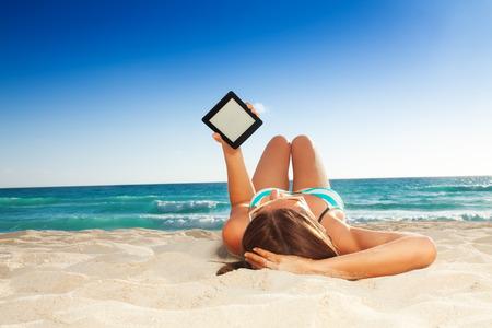 Mooie jonge vrouw die op wit zandstrand en het lezen van haar tablet pc