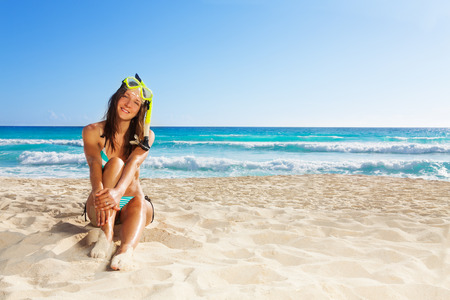 snorkling: Cute woman resting after snorkling sitting on white sand and smiling wearing scuba