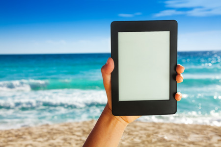 Man hand holding electronic device for reading on white sand beach background