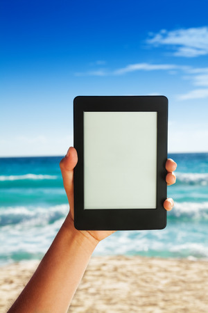 pocket book: Electronic tablet close up on sandy beach background
